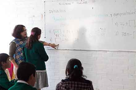 Maestra le enseña en el pizarrón a una alumna de secundaria algunos apuntes de matemáticas