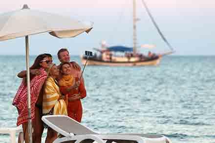 Una familia se toma una selfie a la orilla del mar; al fondo se observa una pequeña embarcación