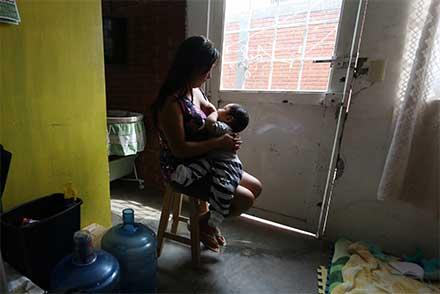 Sentada en una silla, una madre lacta a su bebé en una casa humilde de Oaxaca