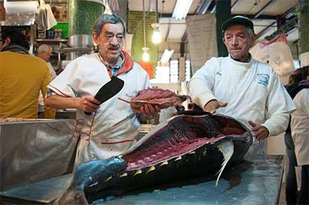Dos vendedores de pescado en el mercado de San Juan filetean un enorme pescado