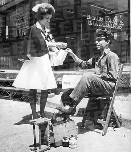 Una mujer pide su donativo para la Cruz Roja a un lustrador d ecalzado en calles del centro de la ciudad de México, fotografía de los alños 50, en blanco y negro