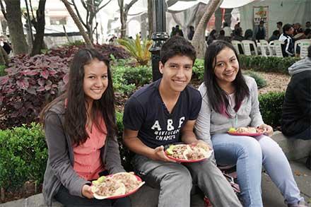 Felices, tres adolescentes, dos mujeres y un hombre, sentados en una banca comen tacos, qué felicidad.