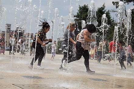 Tres mujeres corren enmedio de los chorros de agua que brotan de la fuente en el piso del Monumento a la Revolución