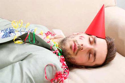 Un hombre acostado en su cama con gorrito, silbatos y serpentinas encima, producto de la fiesta de anoche.