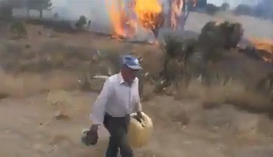 Hombre camina con un bidón en la mano y el fuego se observa detrás