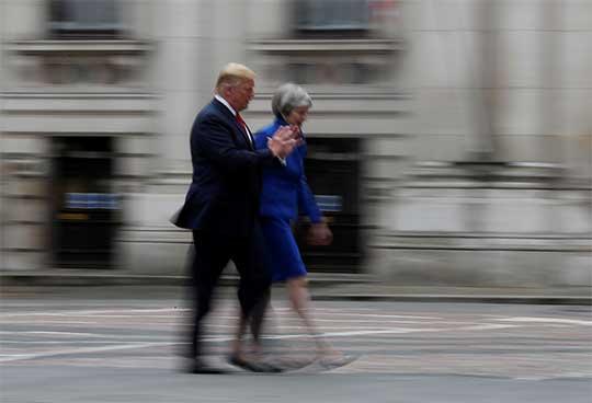 Donald Trump en Londres camina al lado de Theresa may