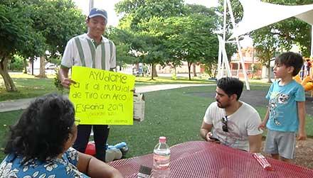 Luis vende chocolates en los parques acompañado de una cartulina