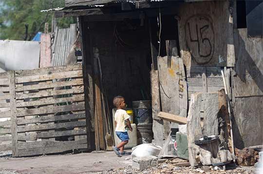 Una casa muy pobre en Nuevo León, un pequeño cruza. La casita está hecha de madera