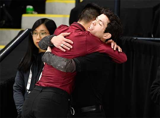 Jugador de hockey sbe hielo se abraza de su entrenador al término de una competencia
