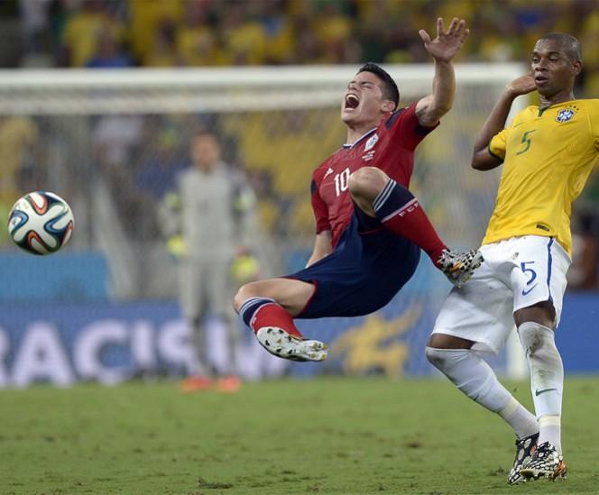 James Rodríguez recibe un fuerte golpe en la espalda durante una entrada de Fernandinho, acción que no fue sancionada por el árbitro. FOTO: AP