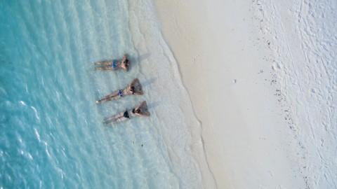 Chicas acostadas en la playa dentro del agua del mar