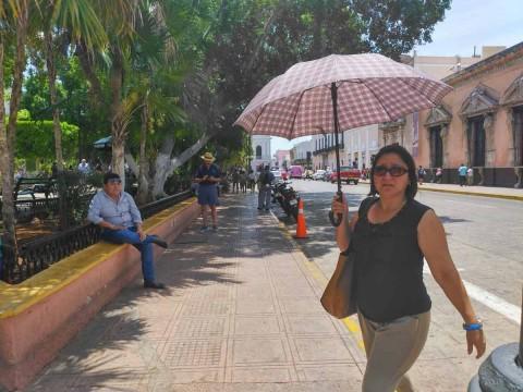 Personas se cubren del sol en Mérida, Yucatán