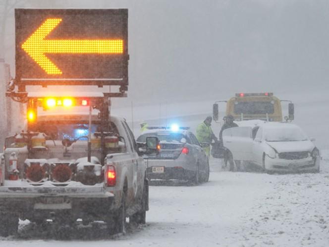 Una persona involucrada en un accidente toma sus pertenencias de su auto sobre la carretera interestatal 95 cerca de Richmond, Virginia. Foto: AP
