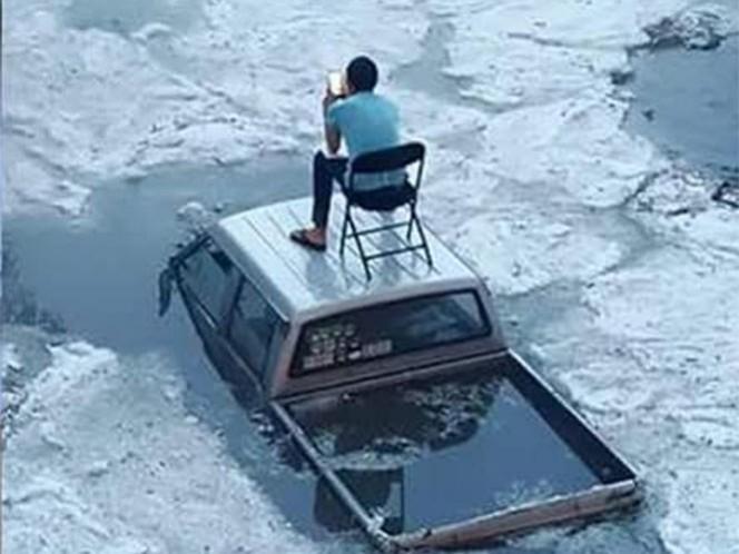En lugar de entrar en pánico o molestarse por la pérdida de su camioneta, colocó una silla sobre su vehículo para esperar su rescate. Foto Karla Méndez