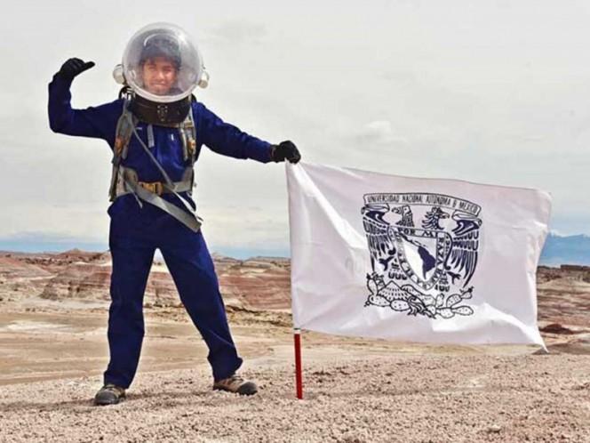 """El estudiante en de la Facultad de Ciencias de la UNAM, Yair Piña, posa con una bandera de la Universidad durante la primera misión análoga a """"Marte""""."""