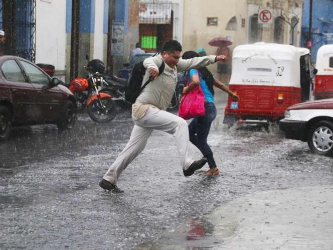 Un hombre brinca un charco durante una tarde de lluvia en Oaxaca.