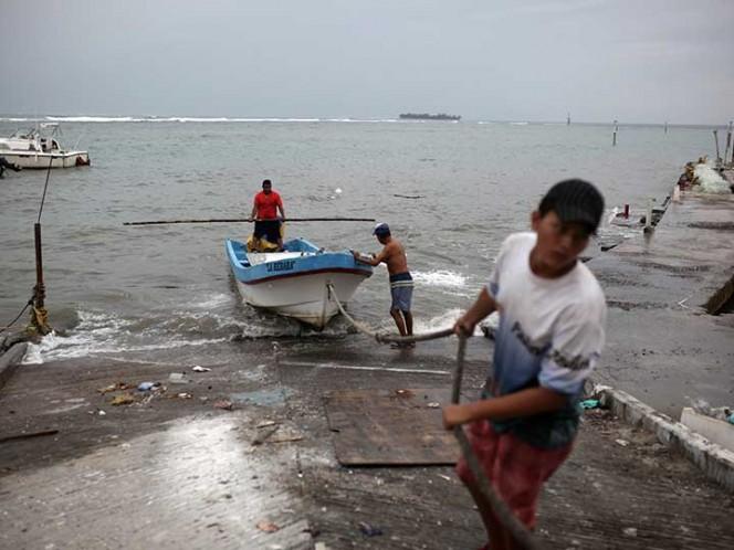 Un grupo de pescadores sacó un bote del mar mientras se preparaba para la llegada del huracán 'Franklin&#039, en Veracruz