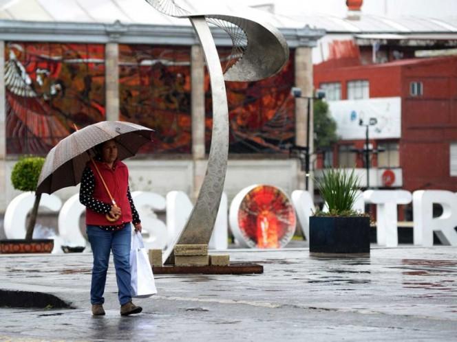 Una mujer se cubre de la lluvia en el Estado de México.