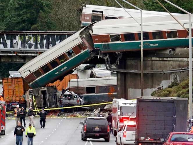 Vagones de un tren Amtrak se ven caídos sobre la Interestatal cinco, junto a varios vehículos destrozados, con algunos vagones aún en las vías más arriba