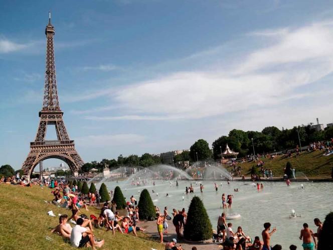 Decenas de personas se refrescaron en la Fuente de Trocadero cerca de la Torre Eiffel en París / Fotos: AFP