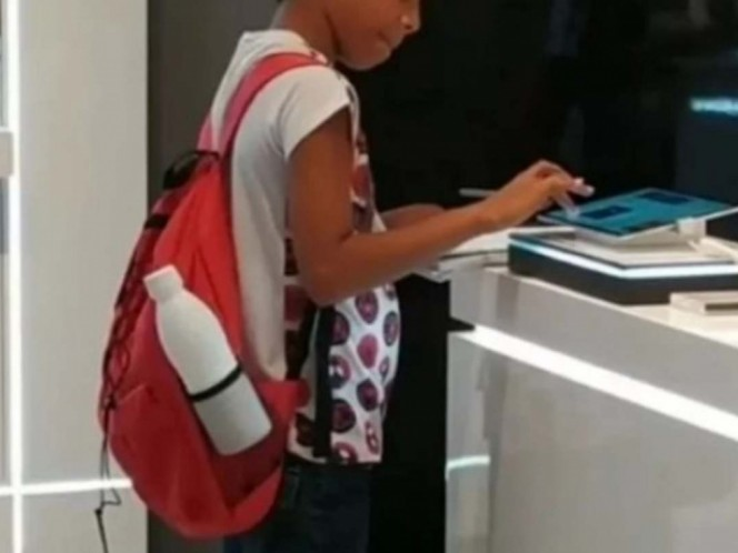 Niño hace tarea en una tienda porque no tiene computadora