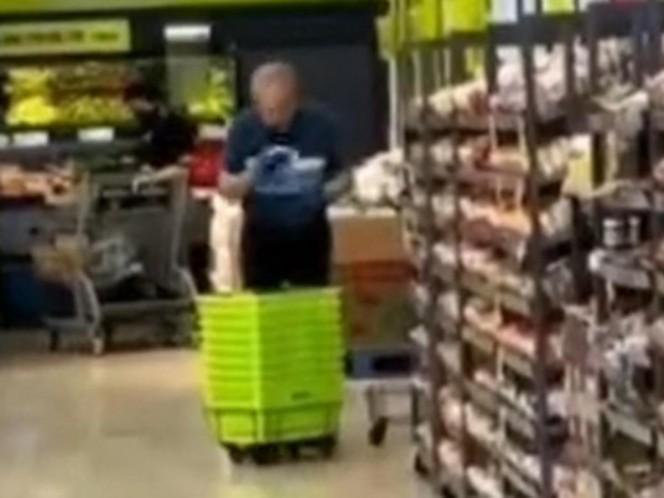 Un empleado de un supermercado limpia las canastas de compras con saliva