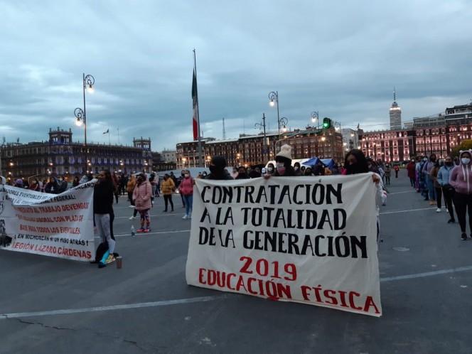Lanzaron consignas con un altavoz y mostraron sus mantas frente a la puerta Mariana de Palacio Nacional. Foto: Jorge González